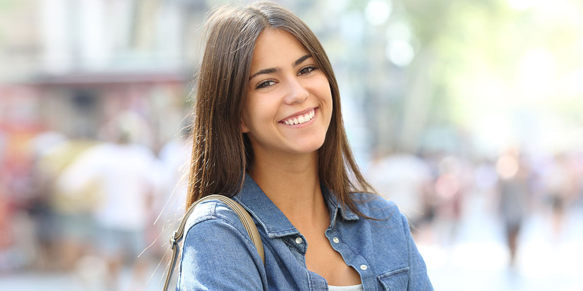 Smiling young woman with bag over sholder